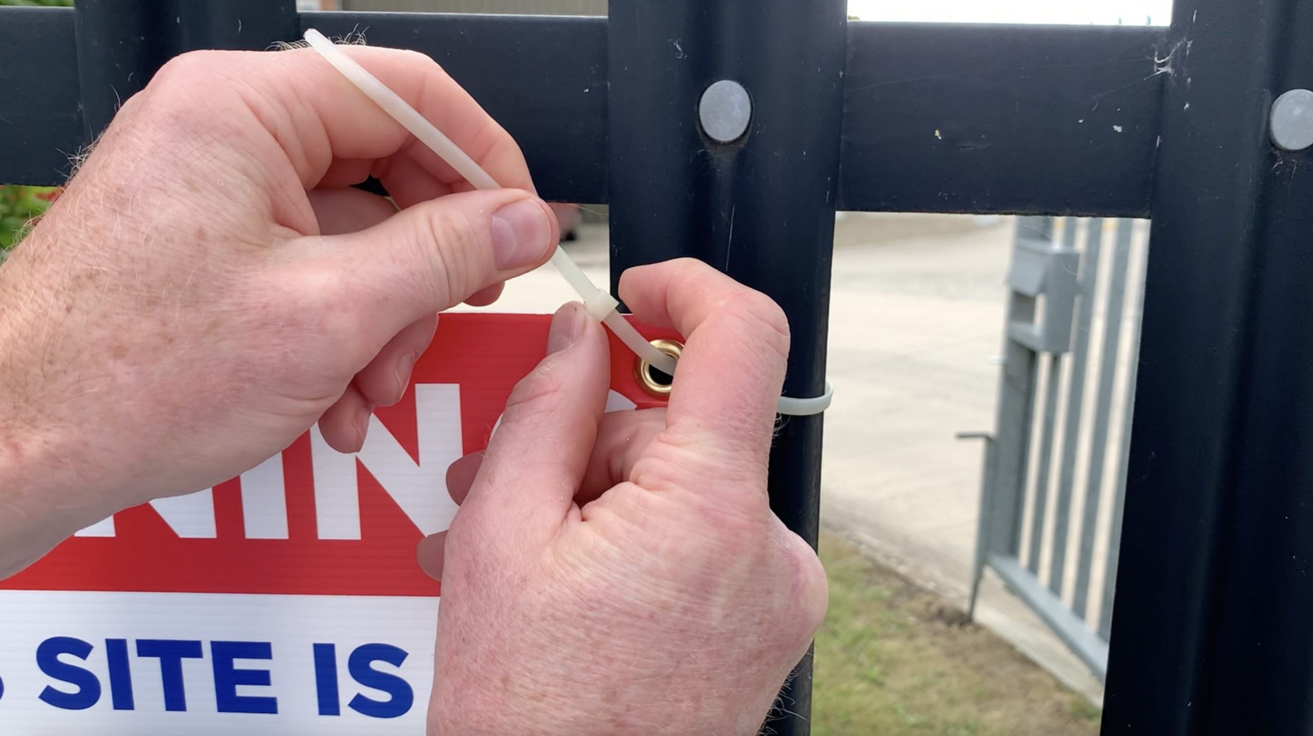 Securing a correx warning board to railings and fences